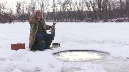 icy : Man enjoy caught fish in the winter.