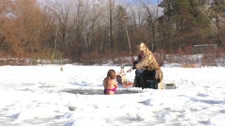 icy : In winter, she catches fish under the ice water. Nearby is a winter fisherman.