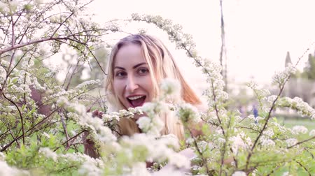 Young beautiful woman peeps from behind a flowering bush and laughs. Wideo