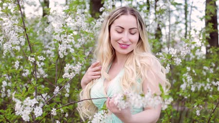 Young beautiful blonde woman admires the blossoming garden among the trees.