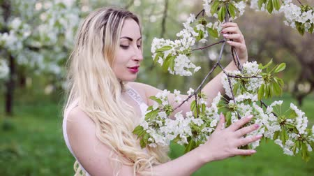 Beautiful young woman enjoys nature in a flowered garden. Wideo