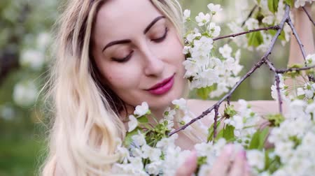 Face of a beautiful blonde woman close-up. She strokes a branch with flower buds in the garden.