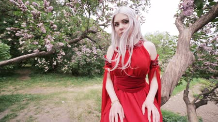 mitologia : Beautiful elf girl in a magic garden sits on a lilac tree. She holds out her hand forward.