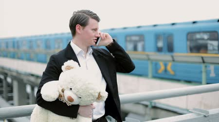 плюшевый мишка : Young man stands near the metro station and talking on mobile phone. In his hands he holds a teddy bear. Стоковые видеозаписи
