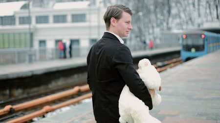 Young man standing outdoors and holding a teddy bear in her arms. A metro train passes by.