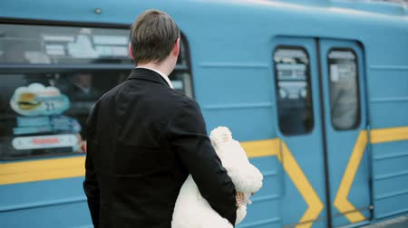 Young man is holding a teddy bear in his hands. He looks after the departing subway car.