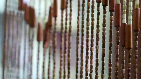 bamboo curtain : Wooden curtains flutter in draft in the doorway. A bamboo curtain sways in the wind. Handmade curtains of wooden beads near. Relaxing background with moving vertical sticks. Interior ecology elements Stock Footage