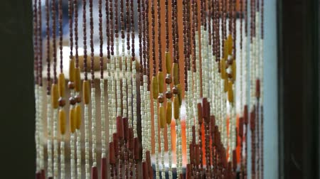 kapualj : Wooden curtains swing  in draft in the doorway. A bamboo curtain sways in the wind. Handmade curtains of wooden beads near. Relaxing background with moving vertical sticks. Interior ecology elements