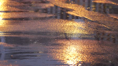 andar : Reflection of human figure on wet asphalt on street at night. Artificial lighting from street lamps. Heavy rain. Rainy weather in autumn city. Bubbles on puddle. Light from headlights of passing cars