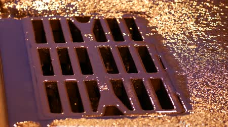 hatch : Drain metal grill on the road during the rain. Pig-iron rusty iron hatch with holes for rainwater drainage. Heavy rain at night on the roadway. Streams of rainwater flow down the drain