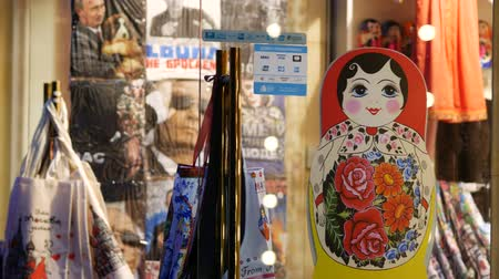 brilhantemente : Moscow, Russia - October 26, 2019: Gift matryoshka in a shop window display. Brightly lit souvenir shop with painted large wooden traditional Russian doll on a shelf behind glass