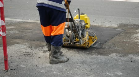 compactor : A worker lays asphalt around a manhole with a hand roller. A man in an orange protective uniform tamps a freshly laid asphalt pavement with a vibro machine compactor. Road repair. Metal sunroof. Stock Footage