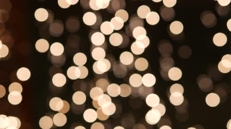 Blurred bokeh holiday lights background. Garland of miniature LED bulbs sway and glows near the glass of the display case. New Year illumination in a shop window. Bright night lights before Christmas