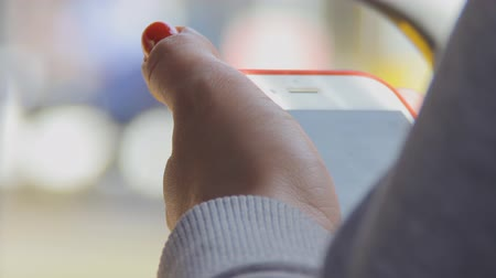 A girl in a light knitted blouse holds a mobile phone in her hands. Smartphone in passenger bus during a stop. A woman is looking at the screen of a gadget. Sunny summer day. Public transport