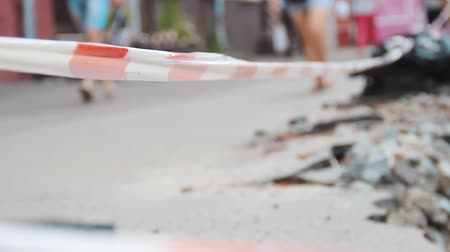 asphalt base : People moving. Warning red and white tapes are stretched for the safety of passers-by around the construction site on the road. Around are pieces of stripped asphalt and heaps of ground. Stock Footage