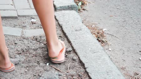 szandál : Female legs in summer slippers. Rubber sandals on the legs of a young girl. A woman stands on the side of the road and steps over. Flip flops on foot. Light shoes for beach. Preparation for vacation Stock mozgókép