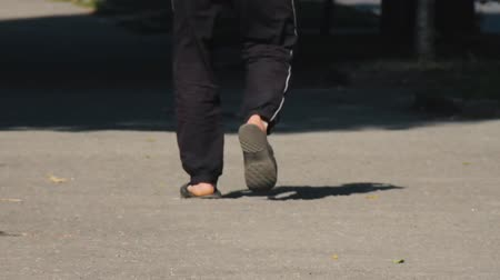 тапочка : A man walks down the street in black sweatpants and flip-flops on his bare feet. Summer warm day. Sunlight. Casual clothes. No faces visible