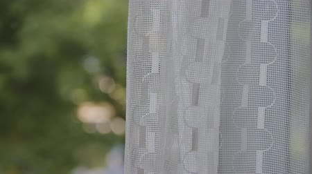 visto : View trough light window curtain. Green trees seen as blurred bokeh background. Focus on structure closeup. Sun rays make their way on waving fabric. Beautiful abstract background for text or images Stock Footage