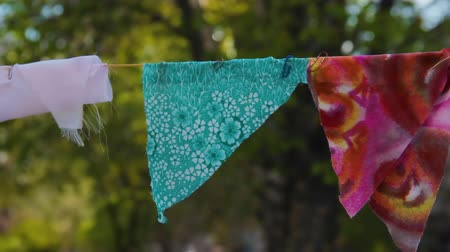 self made : DIY decorations. Do it yourself holiday accessories. Self-made decorative flags of pieces of multi-colored fabric on a rope are fixed with paper clips flying in the wind in open garden. Greens bokeh Stock Footage