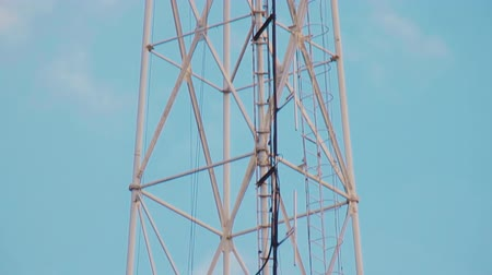 микроволновая печь : Very high radio tower with transmitting VHF and UHF equipment. Cellular link radio transmitters. Steel tower structure painted in red white colors. Staircase for maintenance. Clouds on blue spring sky