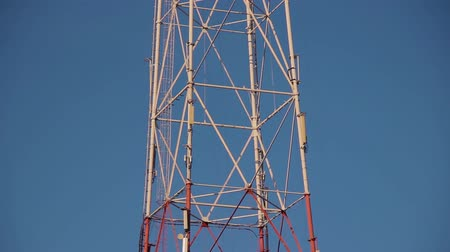 transmitir : Very high radio tower with transmitting VHF and UHF equipment. Cellular link radio transmitters. Steel tower structure painted in red white colors. Staircase for maintenance. Clouds on blue spring sky