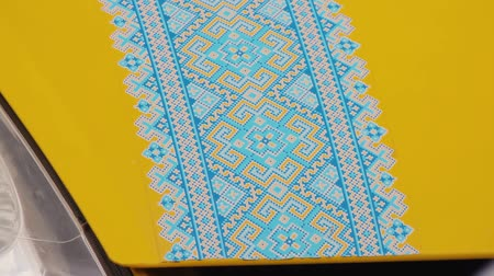 винил : Yellow minivan with applique on the hood in the form of a national Ukrainian pattern. Popular in the period of Maidan embroidery on the car body. Vinyl decal decoration with traditional ornament print