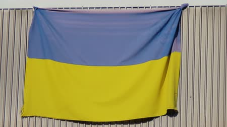 atributo : National flag of Ukraine is hung on balcony of a residential building and flutters in wind. After events on Maidan in 2014 and war in east, patriotic citizens shows flags in windows and near houses Stock Footage