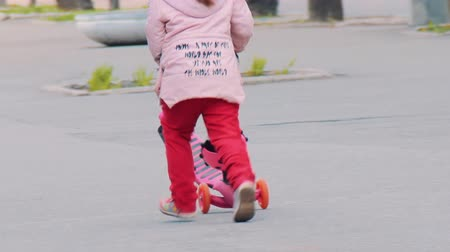 pigtailler : A child on the street runs with a plastic scooter in his hands. A little girl with pigtails in red pants and a pink jacket plays in the city on the sidewalk. Stok Video