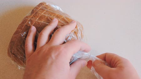 защелка : Male hands open plastic bag with bread on the table. The packaging is closed on a latch.