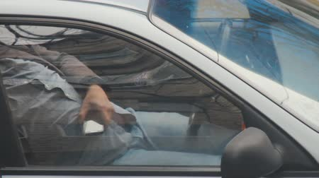 dispatcher : Tired taxi driver resting or sleep in parked car while hold mobile phone in hand. Orders are received through applications or calls in smartphones. Close up through window. Mobile addiction dependency