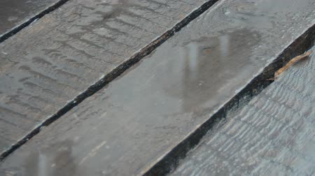 vystavený : Old unpainted boards in the rain. The camera is moving. Raindrops crashing on wood flooring. April rain. Close-up. Nostalgic mood. Extreme macro