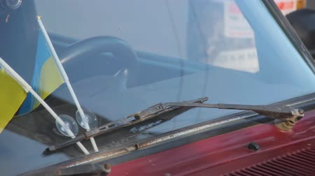 exotikou : Ukrainian national flags attached to auto windshield glass under car wipers.