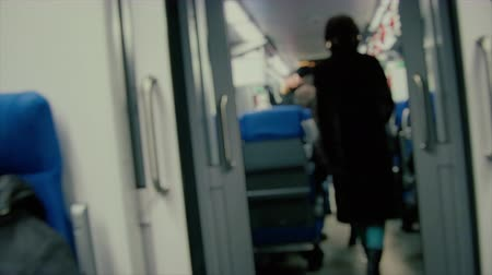 stalker : Blurred unfocused view. Unrecognizable people. A young woman in a black long fur coat with a hood and blue jeans is walking along a train carriage of the Moscow Central Ring Railway (MCC). Stalker concept.
