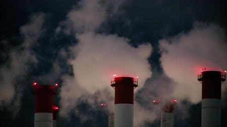 navigational : High-rise red-and-white pipes of a thermal power plant with erupting clouds of steam against the night sky. Navigational red lights to prevent collisions with helicopters and airplanes Stock Footage