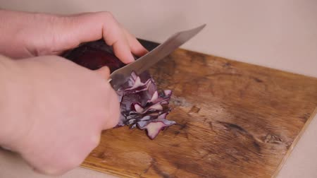 vegetarianismo : A head of red cabbage is cut with a steel knife on a wood kitchen table. Beautiful patterns on the cut slice. Healthy food. Vegetable diet. Vegetarianism