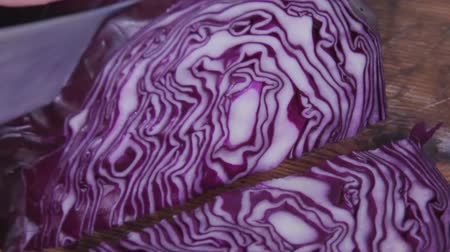 вегетарианство : A head of red cabbage is cut with a steel knife on a wood kitchen table. Beautiful patterns on the cut slice. Healthy food. Vegetable diet. Vegetarianism