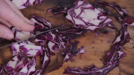 vegetarianismo : A slices of red cabbage is cut with a steel knife on a wood kitchen table. Beautiful patterns on the cut slice. Healthy food. Vegetable diet. Vegetarianism