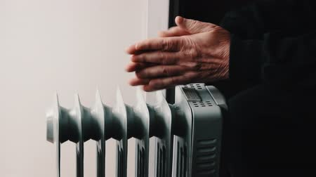 Senior elderly man warms his hands over electric heater. In the off-season, central heating is delayed, so people have to buy additional heaters to keep houses warm despite increased electricity bills