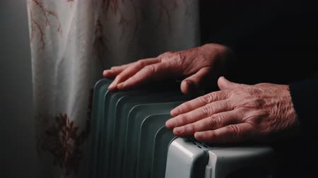 kaloryfer : An elderly man warms his hands over an electric heater. In the off-season, central heating is delayed, so people have to buy additional heaters to keep houses warm despite increased electricity bills.