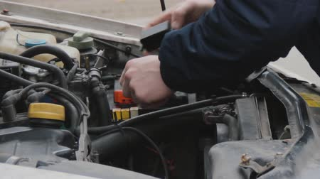 culpa : The driver fixes the malfunction of the car. Raised hood. View of the engine, battery and filler caps and black rubber pipes. Close-up of minor repairs. Mens hands with a tool in a winter jacket.