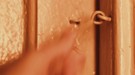 защелка : In the evening, a mans hand opens a wooden door in a house locked on a hook. Incandescent lighting. The wooden door is painted beige. Dark doorway. Primitive door lock