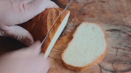 Male hands cut a loaf of white bread on a wooden kitchen cutting board with a steel knife. Man serves bread for breakfast. View from above. Flat lay. Close up