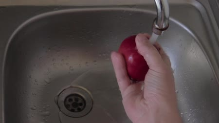 rubs : A man rubs and washes a ripe red apple under running water. Vegetarian preparing snack. Right human hand with fruit above kitchen sink under water flow. View from above. Stainless steel utensils. Stock Footage