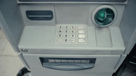cenný : Blinking green slot in gray ATM cash machine. ATM machine is blinking and ready to accept credit card. Metal keypad with digits. Green plastic insert. Protection from hackers. Top view from above