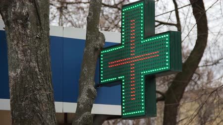 Advertising sign in the form of a green cross with LED animation of green and red. Matrix of colored LEDs. Sign of pharmacy shop on facade of a residential building. Plus signboard on drugstore