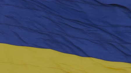 The national flag of Ukraine flutters in the wind on a high flagpole in city. Shooting at close distance range. Real flag in windy afternoon. Independence symbol close up. Sky on background