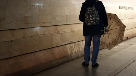 Unrecognizable woman stands on platform of subway with open umbrella and spins it waiting for train. Marble and granite on walls. USSR architecture. Soviet Union station design Stock mozgókép
