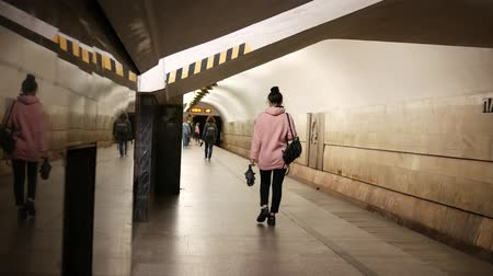 urss : Unrecognizable woman walks along the platform in the subway. Passengers are moving from station to station. Marble and granite on the walls. USSR architecture