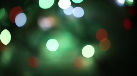 Abstract christmas background in bokeh. Lights of blinking garland in blur. Unsharp bulbs of Christmas decorations on the tree. Festive mood. Animated background for text or pictures. New Year holiday