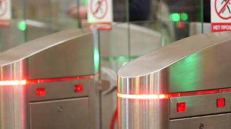 polished : Subway Turnstiles. People pass between the doors. The color indicators blink. Motion sensors. Steel polished surfaces and transparent panels with LED backlight